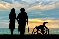 一个残疾轮椅的剪影在偷窥者和近的海附近的 一个残疾人和家的概念老人的 库存例证