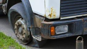 一个残破的前轮,一辆老白色卡车 库存照片