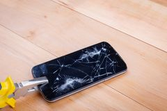 一个残破的智能手机夹紧钳子 在一个木背景 电子修理的概念 库存照片