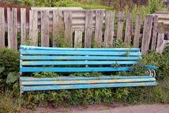 一个残破的蓝色长木凳长满与草在灰色篱芭附近 图库摄影