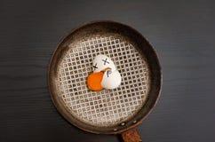 一个残破的鸡蛋的顶视图在煎锅的,溢出的卵黄质,被绘的面孔,食物概念 库存图片