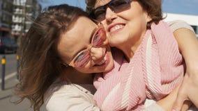 一个母亲和女儿的接近的画象在城市街道上 好日子,戴眼镜的妇女笑并且拥抱 影视素材