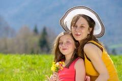 一个母亲和她的女儿有一朵花的在她的嘴 库存照片