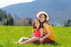一个母亲和她的女儿有一朵花的在他们的嘴 图库摄影