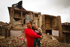 一个母亲和孩子在地震之外在Bhaktap破坏了房子 图库摄影