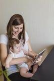 一个母亲和孩子的家庭有一种电子片剂的 库存照片