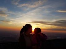 一个母亲的剪影有她的婴孩的日落的 库存照片