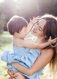 一个母亲的可爱的画象有她的小女儿的光芒的 免版税库存照片
