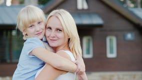 一个母亲的画象有拥抱以他们新的家为背景的一个小女儿的,看照相机 股票视频