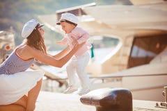 一个母亲的画象有她的使用在跳船的儿子的由海在城市,静物画照片 免版税图库摄影