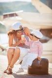 一个母亲的画象有她的使用在跳船的儿子的由海在城市,静物画照片 免版税库存图片