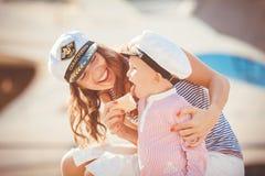 一个母亲的画象有她的使用在跳船的儿子的由海在城市,静物画照片 库存照片