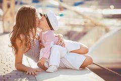 一个母亲的画象有她的使用在跳船的儿子的由海在城市,静物画照片 免版税库存照片