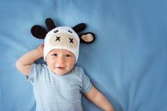 一个母牛帽子的婴孩在蓝色毯子 免版税库存图片
