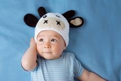 一个母牛帽子的婴孩在蓝色毯子 免版税库存照片