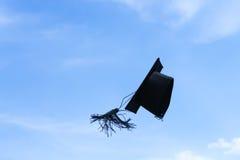一个毕业盖帽或灰浆板被投掷由空气决定,天空背景 免版税库存图片