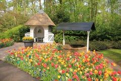 一个水井和pavilon和开花郁金香在花园Keukenhof里在春天 免版税库存照片