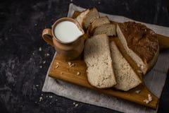 一个水罐的看法牛奶和自创新近地被烘烤的白面包在黑背景 免版税库存图片