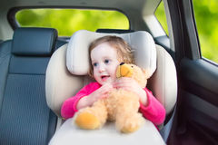 一个汽车座位的逗人喜爱的小孩女孩在假期旅行期间 免版税库存照片