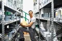 一个汽车维修车间的雇员在备件的一个仓库里 免版税图库摄影