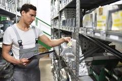 一个汽车维修车间的雇员在备件的一个仓库里 免版税库存照片