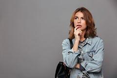 一个沉思十几岁的女孩的画象在牛仔布夹克穿戴了 免版税库存照片