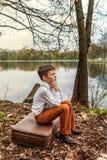 一个沉思的土气笨蛋家伙坐在河湖的银行的一个减速火箭的古板的手提箱 库存图片
