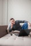 一个沙发的人有膝上型计算机的 免版税库存图片
