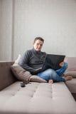 一个沙发的人有膝上型计算机的 免版税库存照片