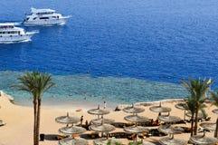 一个沙滩和两艘大白色船,小船,漂浮在海的巡航划线员的顶视图与sunbeds和阳伞的  免版税图库摄影