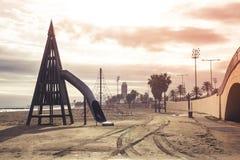一个沙滩的与棕榈树, o一个空的儿童操场 库存图片