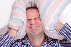 一个沮丧的人在床上 库存照片
