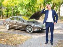 一个沮丧的人在街道上站立在一辆残破的汽车附近并且拿着他的头 外面 免版税库存照片