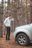 一个沮丧的人,站立在一辆残破的汽车和举行附近他的头 免版税库存图片