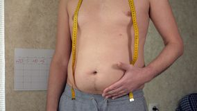 一个油脂人测量他的腰部,一个大啤酒肚,一种健康生活方式拾起肥胖折叠 股票视频