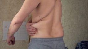 一个油脂人测量他的腰部,一个大啤酒肚,一种健康生活方式拾起肥胖折叠 影视素材