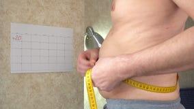 一个油脂人测量他的腰部,一个大啤酒肚,一种健康生活方式 股票视频