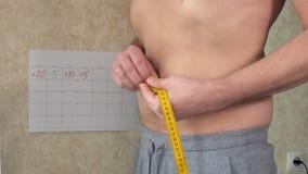 一个油脂人测量他的腰部,一个大啤酒肚,一种健康生活方式 影视素材