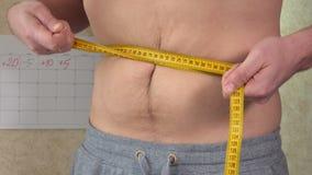 一个油脂人测量他的腰部,一个大啤酒肚,一种健康生活方式 股票录像