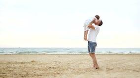 一个沿含沙海滨的小的快乐的男孩奔跑对他的父亲 与孩子的愉快的爸爸戏剧,培养他在他的胳膊 股票视频