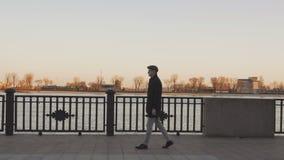 一个沿堤防的庄重装束人步行沿河在春天晚上 影视素材