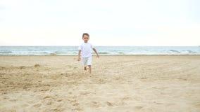 一个沿沙滩的小的愉快的男孩奔跑反对海在一好日子 孩子跑遇见照相机 股票视频