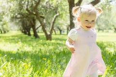 一个沿草的逗人喜爱的婴孩奔跑 背景概念框架沙子贝壳夏天 库存照片