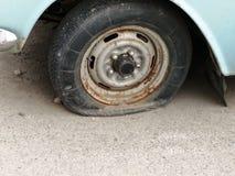 一个泄了气的轮胎 老减速火箭的轮子 免版税图库摄影