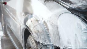 一个洗车过程的慢动作录影在自助洗车的 人洗涤他的汽车他自己 水喷气机与 影视素材