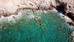 一个洞的鸟瞰图与透明的波浪的在与清楚的大海的岩石海岸 影视素材