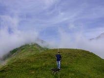 一个活跃年长人在山的步行与他的狗 免版税库存图片
