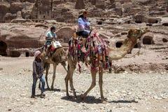 一个流浪的男孩在乘坐骆驼的一个小组游人旁边走通过Petra古老废墟在约旦 图库摄影