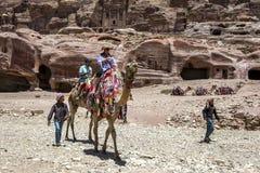一个流浪的男孩在乘坐骆驼的一个小组游人旁边走通过Petra古老废墟在约旦 库存照片