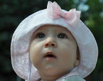一个浅粉红色的帽子的逗人喜爱的女婴有弓的想知道天空的 免版税库存照片